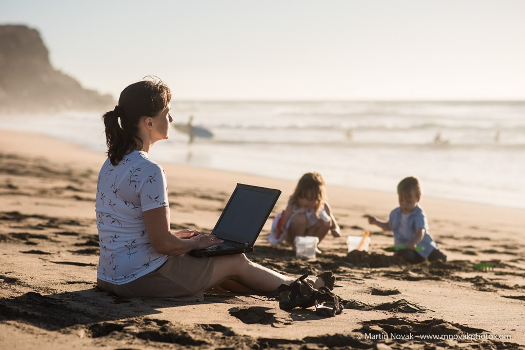 fe51b33ac274 Mother working on laptop with children playing in sand on beach by sea